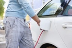 Mann steckt Stromstecker seitlich in ein weißes Auto