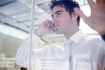 Mann steht an Glaswand und telefoniert
