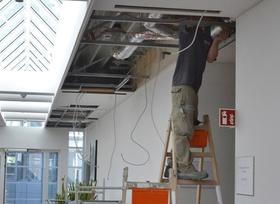 Mann steht auf Leiter und arbeitet