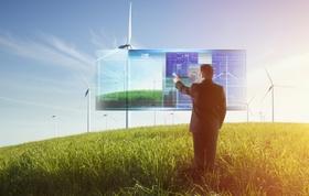 Mann steht auf Wiese vor Bildschirm und Windpark