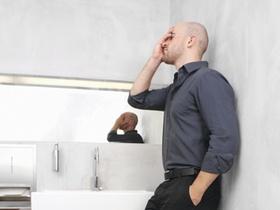 Mann steht erschoepft in Waschraum