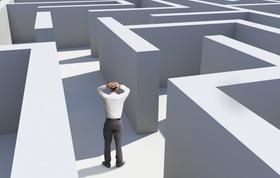 Mann steht in Labyrinth und schlägt Hände über dem Kopf zusammen