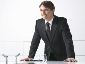 Mann steht laechelnd im Buero an Konferenztisch