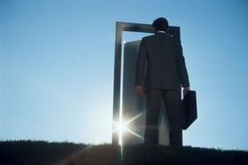 Mann steht mit Aktenkoffer vor einem Türrahmen