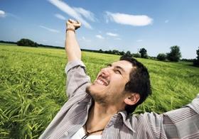 Mann steht mit ausgestreckten Armen in Getreidefeld, freut sich