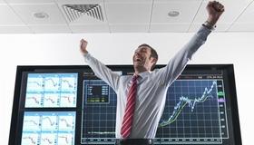 Mann steht vor Bildschirm und reißt die Arme hoch