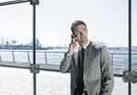 Mann telefoniert mit Handy in Buerogebaeude vor Glasfront, Hafen im Hgr.