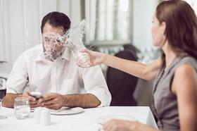 Mann tippt am Handy Frau schüttet ihm ein Glas Wasser ins Gesicht