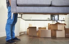 Mann trägt Couch in Wohnung