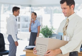 Mann trägt nach Kündigung seine Arbeitsmaterialien aus Büro