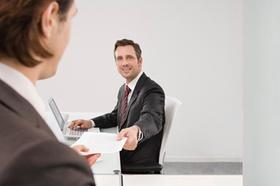 Mann übergibt anderem Mann ein Dokument
