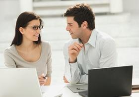 Mann und Frau sitzen an Laptops, unterhalten sich