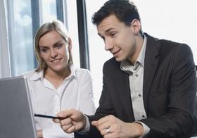 Mann und Frau sitzen im Büro an Laptop