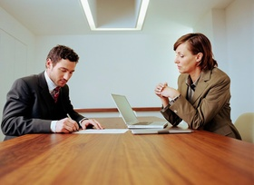 Businessman and woman in meeting, laptop on table
