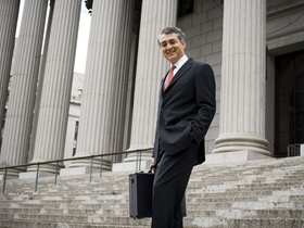 Low angle view of a male lawyer standing on the steps of a courthouse and smiling