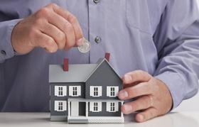 Mann wirft Münze in kleines Hausmodell