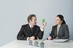 Mann zeigt Frau Bauklötzchen Häuschen als Modell oder Prototyp