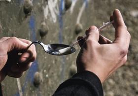 Mann zieht Spritze mit Heroin aus Loeffel auf, Detail