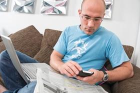 Mann zu Hause mit Stellenanzeigen, Laptop und Handy