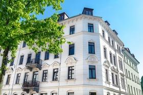 Mehrfamilienhaus Altbau weiß blauer Himmel