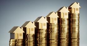 Mehrfamilienhaus Modell mit angehäuften Euro-Münzen davor