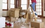 Mensch auf Leiter in Raum mit Kartons