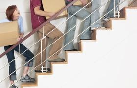 Menschen tragen Kartons eine Treppe hinauf
