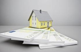 Mini Hausmodell das auf Geldstapel steht