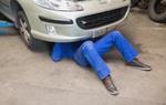 Minijobber der in Werkstatt Auto repariert