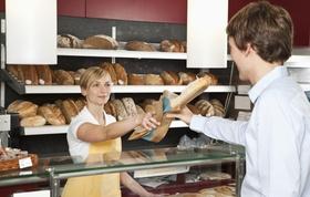 Minijobberin die in einer Bäckerei Baguette verkauft