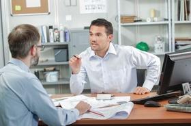 Mitarbeiter diskutieren an Schreibtisch über Pläne