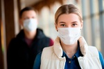 Man and woman wearing protective mask against transmissible infectious diseases and as protection ag