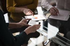 Mitarbeiter sitzen an Tisch und halten Grafiken auf Devices in der Hand
