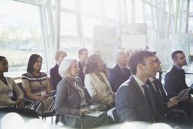Mitarbeiter sitzen bei Konferenz zusammen und hören zu