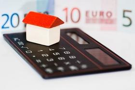 Modell-Haus Taschenrechner Geld im Hintergrund Wohngeld