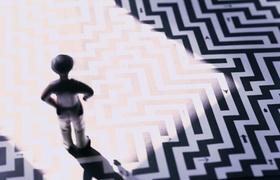 Modellmensch steht auf gedrucktem Labyrinth auf welches die Sonne scheint