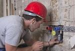 Ein Installateur, Anlagenmechaniker für Sanitär-, Heizungs- und Klimatechnik, verlegt eine Abwasserl