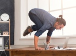 Short break for yoga in office. Flexible man practicing yoga at workplace, making balance exercise o