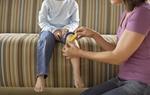 Mutter klebt Pflaster auf Knie der auf Couch sitzenden Tochter