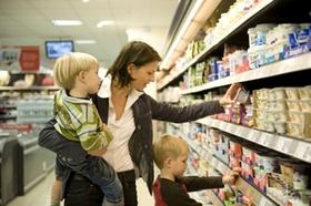 Mutter mit Kindern vor Supermarktregal