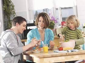Mutter mit Kindern zu Hause beim Essen