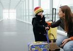 Mutter und Sohn stehen mit Koffern in einem Uebergang am Flughafen