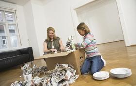 Mutter und Tochter packen Umzuskarton mit Geschirr aus