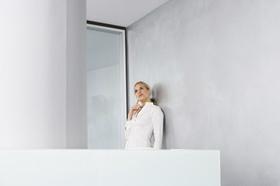 Nachdenkliche Frau auf Balkon eines modernen Gebäudes