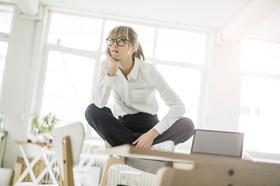 nachdenkliche Frau sitzt auf Tisch