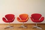 Orangene und Rote Sessel in einer Reihe