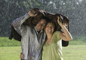 Paar steht unter Jacke im Regen