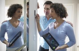 Paar steht vor Schalter und Frau bedient diesen mit Tablet in der Hand