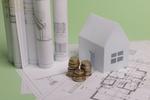 Papierhaus mit Münzen und Bauplan
