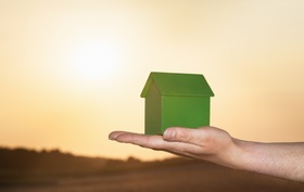 Person hält grünes Modellhaus auf der Hand